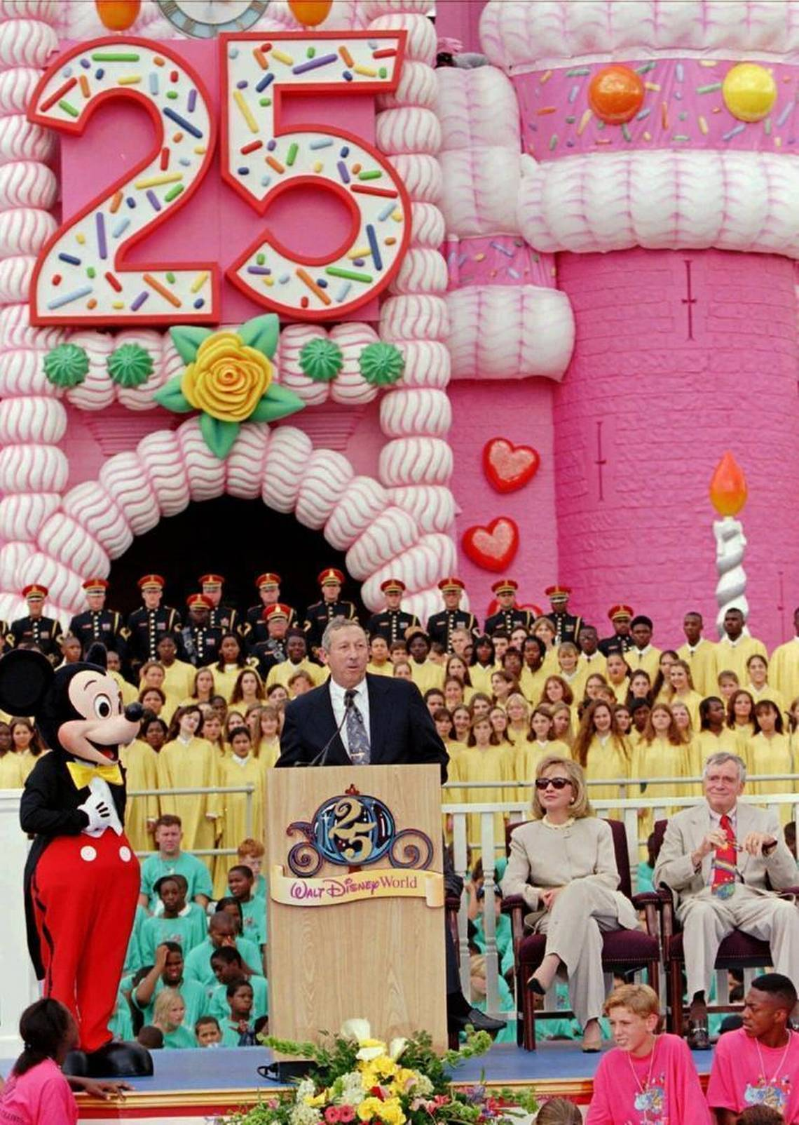 Roy Disney, second from left, nephew of Walt Disney, addresses the crowd along with Mickey Mouse, First Lady Hillary Rodham Clinton, and Fla. Governor Lawton Chiles during the 25th anniversary rededication ceremonies Tuesday, Oct. 1, 1996, at Walt Disney World in Lake Buena Vista, FL
